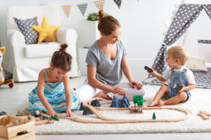 mum building wooden railway with children